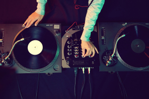 Dj hands on equipment deck and mixer with vinyl record at party